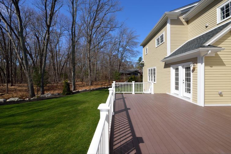 Large composite deck attached to a colonial-style home.