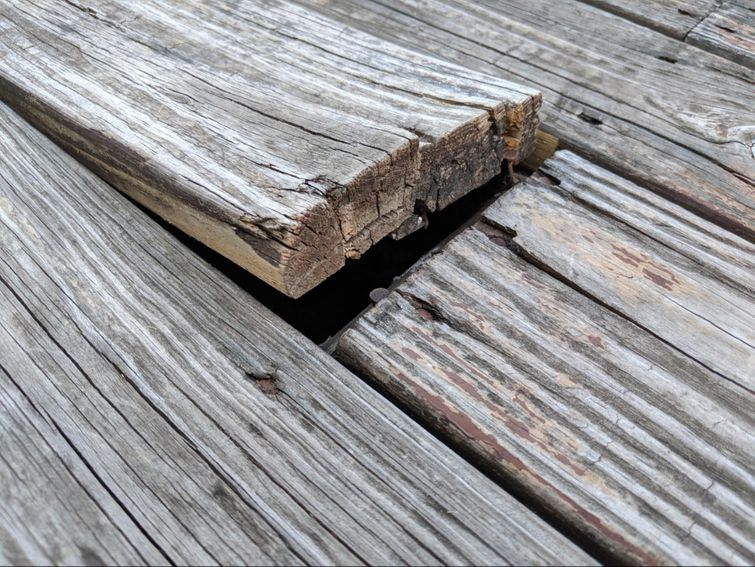 Wood deck warping and in need of repairs.